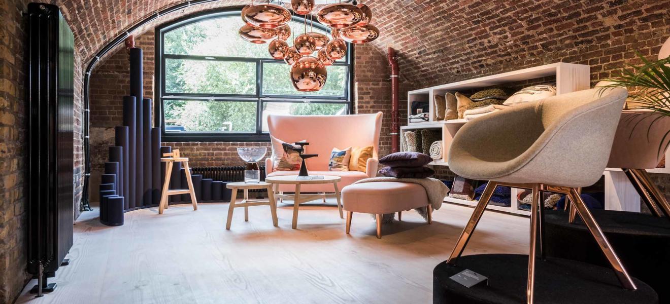 Innenansicht des Shops von Tom Dixon. Backsteingewölbe, Holzboden und coole Möbel und Leuchten.