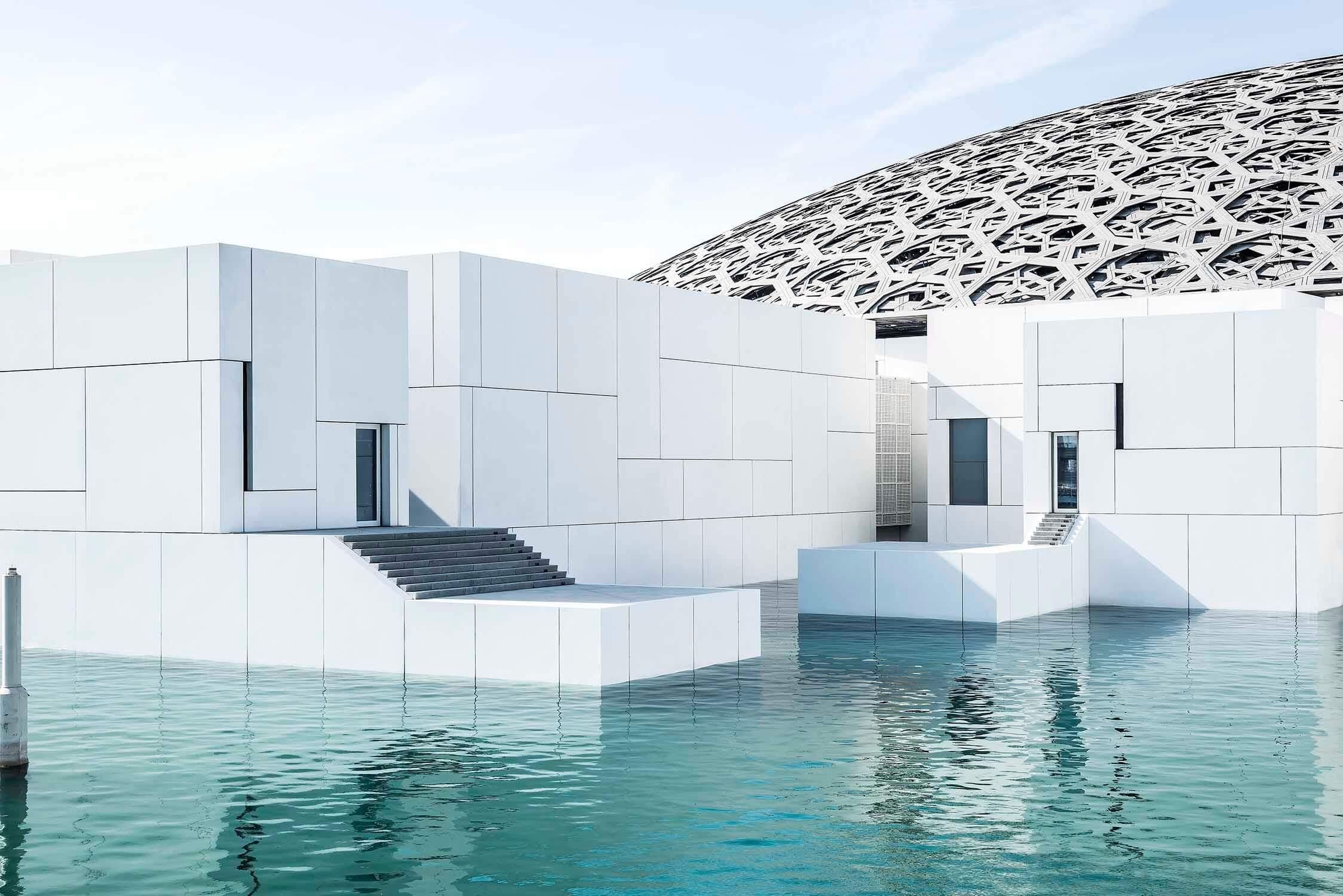 Aussenaufnahme vom Kunstmuseum Louvre von Jean Nouvel in Abu-Dhabi. Weisse Baukörper mit riesigem Kuppeldach, umgeben von türkisfarbenem Meerwasser.