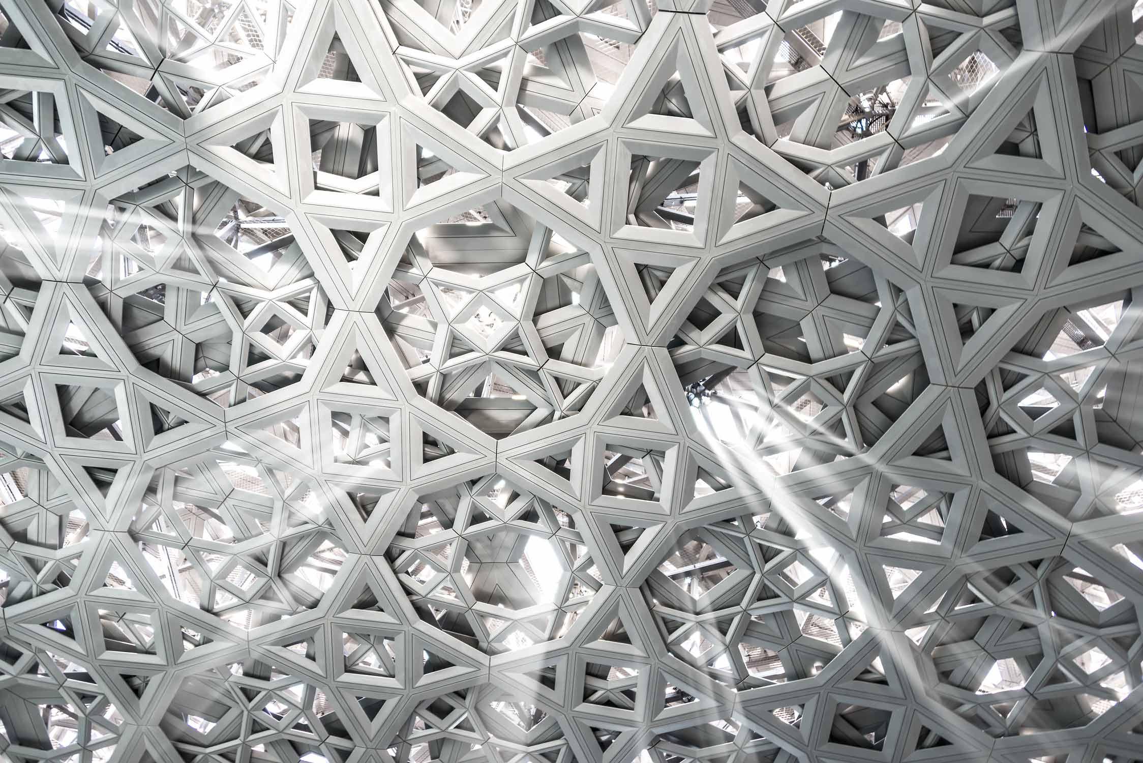 Detail vom Kuppeldach im Kunstmuseum Louvre von Jean Nouvel in Abu-Dhabi. Das Kuppeldach lässt Lichtstrahlen eindringen, wie einen Lichtregen.