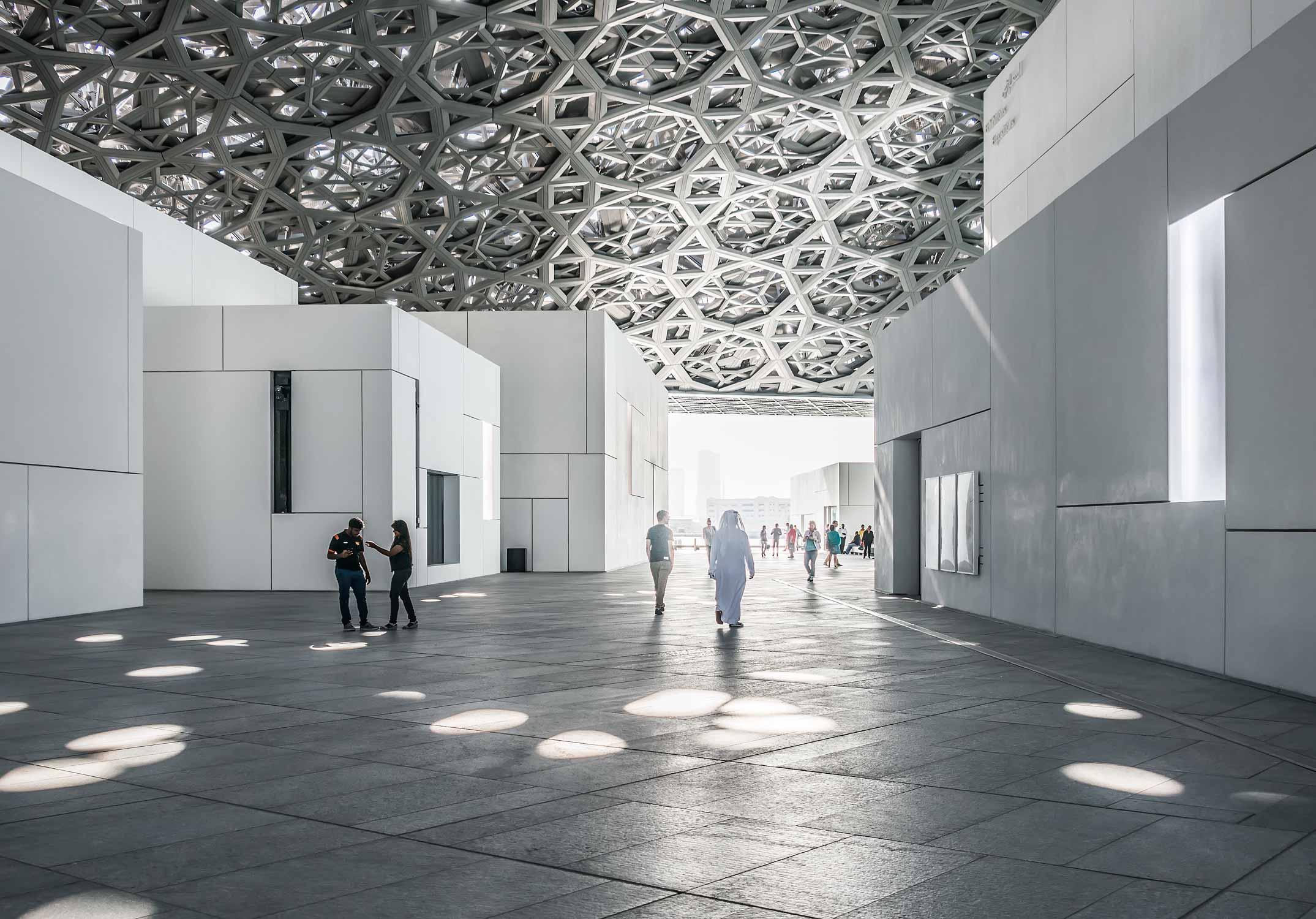 Innenhof im Kunstmuseum Louvre von Jean Nouvel in Abu-Dhabi. Weisse Baukörper mit riesigem Kuppeldach, das Lichtstrahlen, wie einen Lichtregen durchlässt.